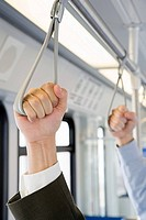 People holding handles on train