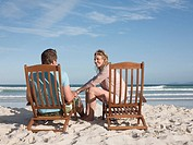 Couple on lounge chairs on the beach