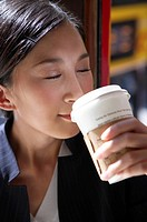 Young Businesswoman Riding Tram, Holding Coffee Cup, Eyes Closed