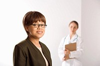 African American middle_aged female patient woman smiling looking at viewer with Caucasian mid_adult female doctor standing in background