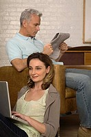 Woman using laptop computer with man reading newspaper