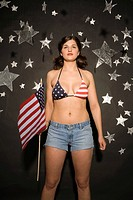 Young woman holding American flag, portrait