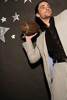 Businessman throwing football