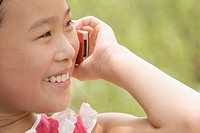 Close_up of a girl talking on a mobile phone and smiling