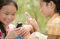 Close_up of two girls using their mobile phones