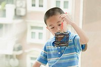 Close_up of a boy holding a birdcage with a bird in it