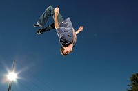 Young man jumping in mid_air, low angle view