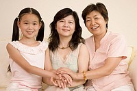 Girl with her mother and grandmother stacking their hands and smiling