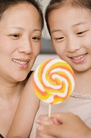 Close_up of a girl holding a lollipop with her mother