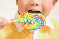 Close_up of a boy eating a lollipop