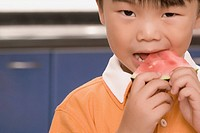 Close_up of a boy eating watermelon