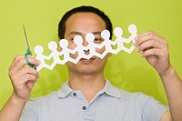 Close_up of a male office worker holding a pair of scissors and a paper chain