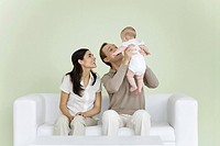 Parents sitting together on sofa, man holding baby (thumbnail)