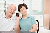 Close_up of a mature couple smiling and holding a mobile phone