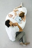Parents and baby relaxing on ottoman, baby holding mother's hand, overhead view