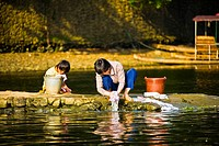 Young woman with her daughter washing clothes at a riverside, Li River, XingPing, Yangshuo, Guangxi Province, China