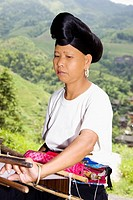 Close_up of a mature woman weaving a carpet, Jinkeng Terraced Field, Guangxi Province, China