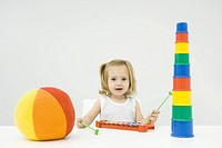 Toddler girl sitting with toys, playing xylophone, smiling at camera