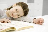 Girl sitting at table with book, resting head on arm, smiling at camera