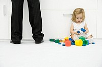 Toddler girl sitting on the ground beside father's legs, playing with toys