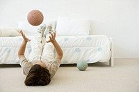 Boy lying on the ground in bedroom, throwing ball in the air
