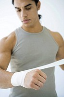 Man wrapping bandage around his wrist, looking down (thumbnail)