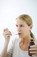 Mature woman taking a spoonful of medicine