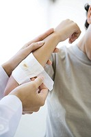 Doctor applying gauze to child's arm, cropped view