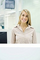 Businesswoman standing behind counter, smiling at camera, portrait (thumbnail)
