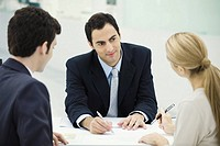 Meeting between professional and clients, woman preparing to sign document