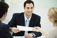 Meeting between professional and clients, man passing document to woman