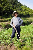 Mature woman standing in a field and smiling, Emerald Valley, Huangshan, Anhui Province, China