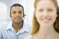 Professional man wearing headset smiling at camera, female colleague in foreground