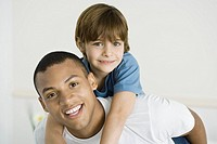Young man giving boy piggyback ride, both smiling at camera