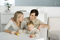 Family at table, boy playing with toy trucks, parents smiling at each other