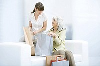 Senior woman and young adult woman holding shopping bags, smiling at each other