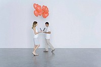 Man and woman walking toward each other with laptop computers and heart balloons, smiling