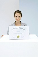 Woman displaying certificate of achievement