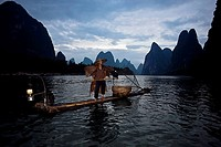 Fisherman standing on a wooden raft in a river, Li River, XingPing, Yangshuo, Guangxi Province, China