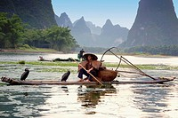 Fisherman fishing in a river with a hill range in the background, Guilin Hills, XingPing, Yangshuo, Guangxi Province, China