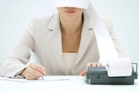 Accountant using adding machine, printout wrapped around her face like blindfold, cropped view