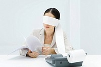 Female accountant blindfolded with paper from adding machine, holding document