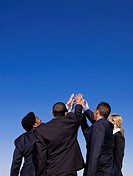 Business people standing outdoors joining hands