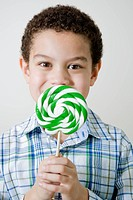 Mixed race boy with oversized lollipop