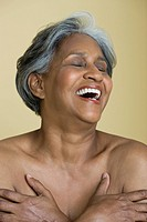 African woman covering chest and laughing