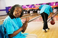African woman rubbing aching wrist in bowling alley