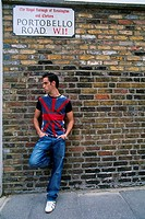 England _ London _ Notting Hill district _ Portobello Road _ young man leaning against brick wall