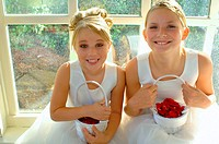 Elevated view on two blond smiling little flower girls with rose petals