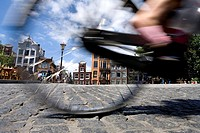 Low section view of person cycling with buildings in city, North Holland, Amsterdam, Netherlands