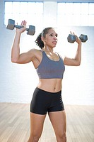 Muscular young woman is lifting weights in gym.